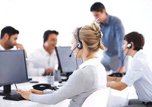 Business woman wearing headset working on computer with colleagues in background
